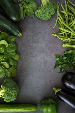 Green vegetables, healthy, vegetarian food. parsley, basil, cucumber, broccoli, green bell pepper, zucchini, bean sprouts, spinach. Top view heathy raw food frame, leaf vegetables on dark background Banco de Imagens