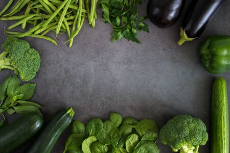 Green vegetables, healthy, vegetarian food parsley, basil, cucumber, broccoli, green bell pepper, zucchini, bean sprouts, spinach. Top view heathy raw food frame, leaf vegetables on dark background