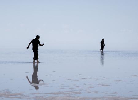 Silhouette of two men walking on the salt lake.
