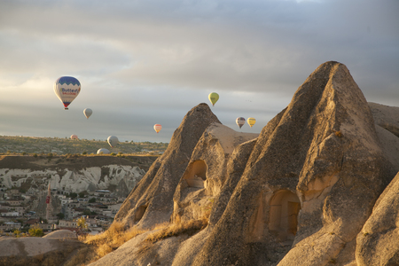 Multi-coloured hot air balloons floating and flying in the air above a mountain.
