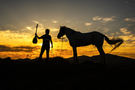 A silhouette of a man holding a musical instrument and a horse during a sunset.