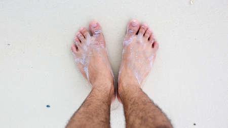 pies masculinos: pies masculinos en el fondo de arena blanca Foto de archivo