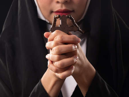 Close up of Christian, Catholic nuns holding rosary ,cross, in the praying hands. Prays in silence with faith and devotion. Religion concept.