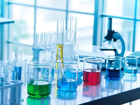 grüne, blaue, rote und dunkelblaue Farbflüssigkeit in einem Becherglas und eine gelbe in einer Röhre im Labor, damit die Forscher ihre Arbeit machen können.