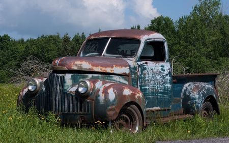 jalopy: An old truck abandoned in a field