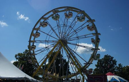 A ferris wheel at a fair against a blue sky