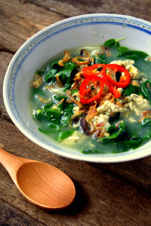 Confinement Soup -Egg soup with vegetables Asian Style on wooden background