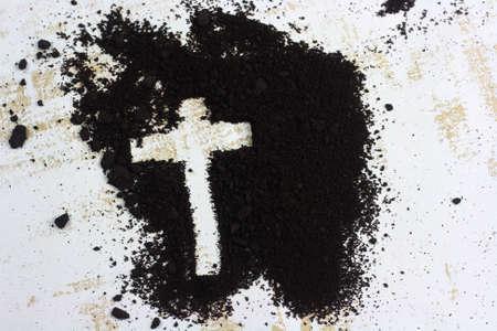 Cross written in ash and wooden Christian cross symbol as a religion concept Standard-Bild
