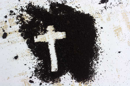 Cross written in ash and wooden Christian cross symbol as a religion concept Stock Photo
