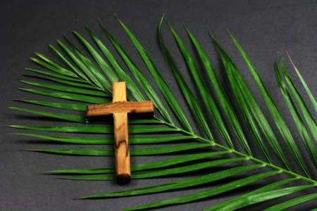 Easter wooden cross on black background , religion Palm Sunday concept