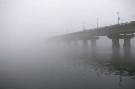 obscuring: View of entire length of bridge with fog obscuring top of bridge. Stock Photo
