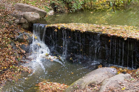 Waterfall in the wood in autumn photo