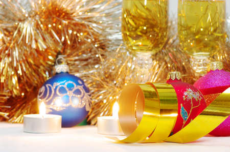Two glasses of champagne lightening with candle in new year stuff with christmas balls photo