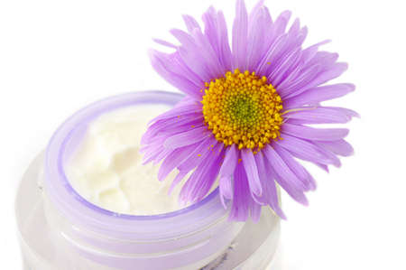 Closeup of open container of cosmetic face cream on white backround with violet camomile on the top photo