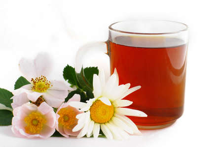 Herbal tea in cup of glass with dog-rose and camomile flowers on a white background. photo