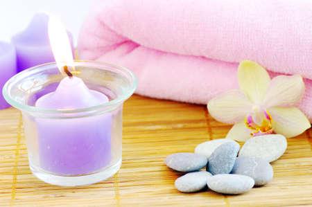 Spa-Konzept mit Kerzen Orchideen Handtücher und Steine auf nassem Holz Hintergrund
