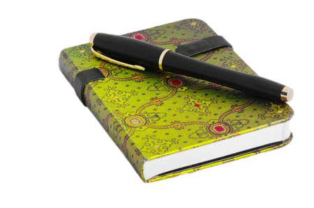 アラビア語緑の飾りと白いテーブル上のペンとメモ帳 写真素材