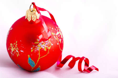 red christmas ball with red ribbon on the white background  photo