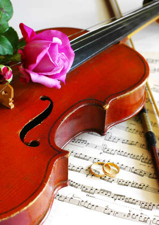 wedding rings and pink roses with violin on the note photo