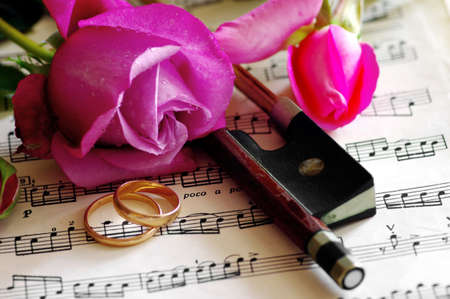 Gold wedding rings and pink rose on the note photo