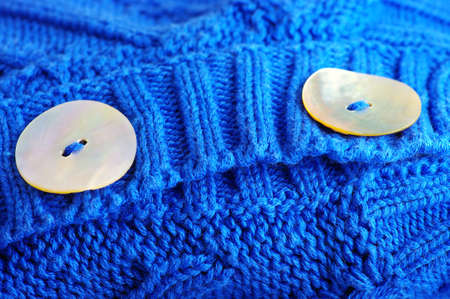 closeup of a wavy blue knitted fabric with buttons of bone Stock Photo - 12401707