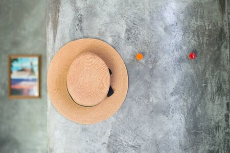 imply: selective focus of hat hanging on the cement textured wall, imply to relax and vacation
