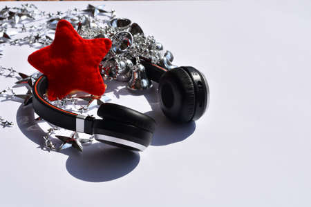 Headphones and silver Christmas decoration on white background. Top view, copy space.