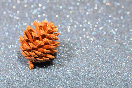 Brown pine pineapple over silver background, Christmas time, Christmas decoration