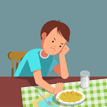 A little boy refusing food, kid does not want to eat. The boy sits at the table and does not want to eating