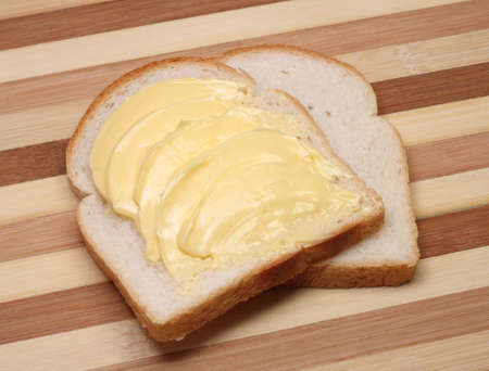 Delicious white bread and yellow butter on cutting board  Stock Photo
