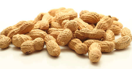 Close up of roasted peanuts in the shell on white background Stock Photo