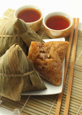 Three rice dumplings and chinese tea on bamboo placemat