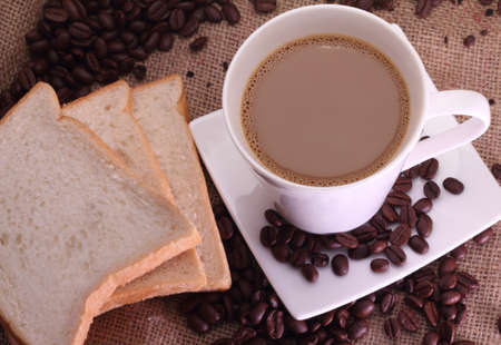coffee milk, coffee beans and some breads on sack burlap background