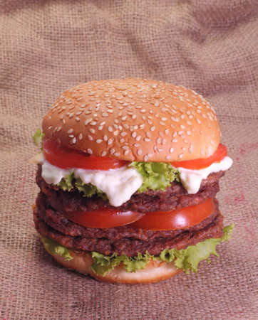 Handmade double meat burger with vegetable and tomatoes on sack burlap background