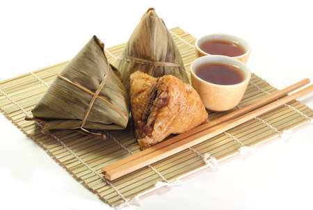 Three rice dumplings and chinese tea on bamboo placemat Stock Photo