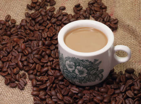 Traditional chinese nanyang style coffee and coffee beans on sack burlap background. Stock Photo