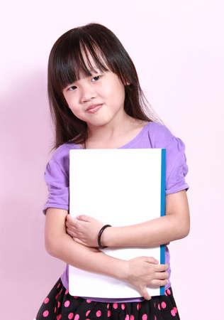 A cute little girl holding a book