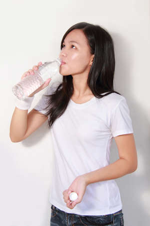 young lady drinking a bottle of mineral water photo