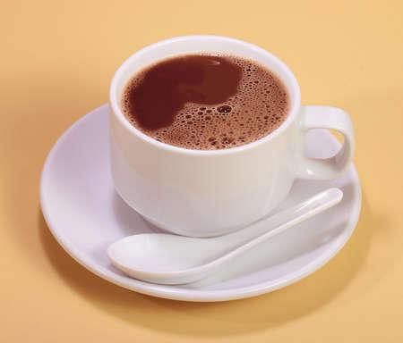 chocolate caliente: Una taza de bebida de chocolate caliente en la simple fondo de color amarillo Foto de archivo