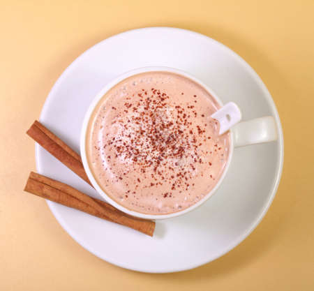 Hot chocolate milk drink and cinnamon on a yellow background photo