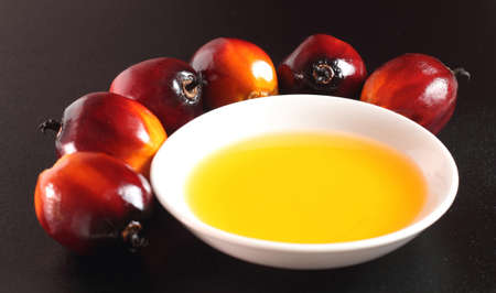 Oil Palm: Oil palm fruits and a plate of cooking oil on black background Stock Photo