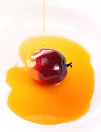 Oil plam fruit with drops of oil on white background photo