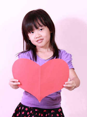 A cute little girl holding a heart shape paper photo