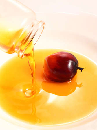 A bottle of palm cooking oil pouring in a white plate photo
