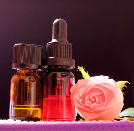 Two bottles essential oil and rose flower on bamboo mat, come on, lets go spa.