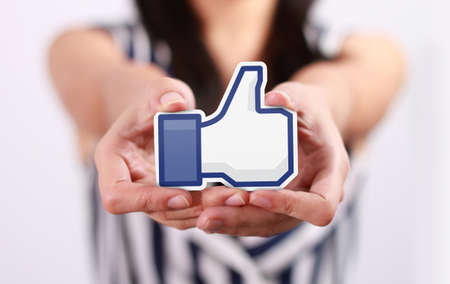 Johor, Malaysia - July 21, 2013: This like icon button is the voting system used to rate user comments on Facebook. Low Shu Ching hand holding like icon on July 21, 2013 in Johor, Malaysia. Editorial