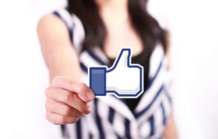 Johor, Malaysia - July 21, 2013: This like icon button is the voting system used to rate user comments on Facebook. Low Shu Ching hand holding like icon on July 21, 2013 in Johor, Malaysia.