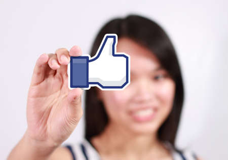 shu: Johor, Malaysia - July 21, 2013: This like icon button is the voting system used to rate user comments on Facebook. Low Shu Ching hand holding like icon on July 21, 2013 in Johor, Malaysia. Editorial