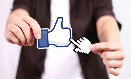 Johor, Malaysia - July 21, 2013: This 'like' icon button is the voting system used to rate user comments on Facebook. Low Shu Ching hand holding like icon on July 21, 2013 in Johor, Malaysia.