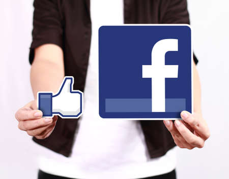 admiration: Johor, Malaysia - July 21, 2013: As of today,  Facebook is the largest social media network on the web. A woman hand holding Facebook icon on July 21, 2013 in Johor, Malaysia.
